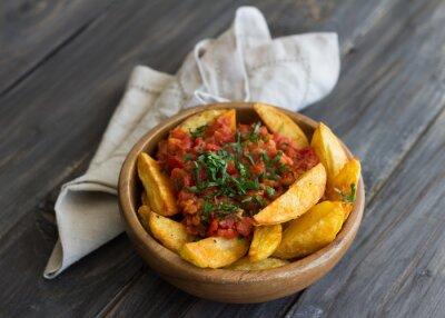 Cuadro Patatas Bravas, tapas tradicionales españolas, papas al horno con salsa de tomate picante en un tazón de madera en la mesa de madera. enfoque selectivo