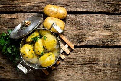Cuadro Patatas hervidas con hierbas en la mesa de madera. Espacio libre para el texto.