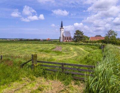 Pequeña iglesia blanca de Den Hoorn en la isla holandesa de Texel, visto desde un prado