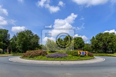 Pequeña rotonda con las plantas, los árboles y la señal de tráfico sin tráfico, contra un hermoso cielo azul