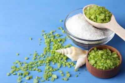 Cuadro Perfumada sal de mar verde y blanco es en un tazón de vidrio y bowl.Scattered de madera alrededor de la sal del mar verde con conchas de mar sobre una mesa de madera azul con conchas de mar