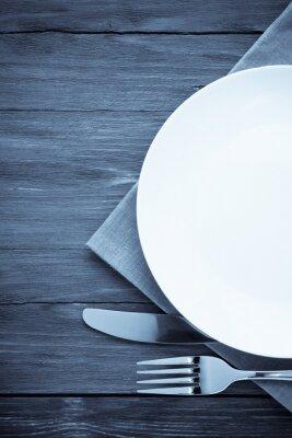 Cuadro placa blanca, cuchillo y tenedor en la madera