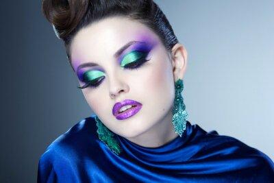 Cuadro profesional de maquillaje azul y peinado en el rostro de mujer hermosa