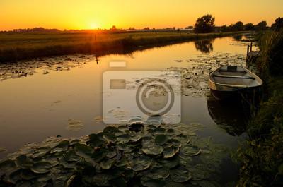 Puesta de sol sobre una zanja con un barco y nenúfar