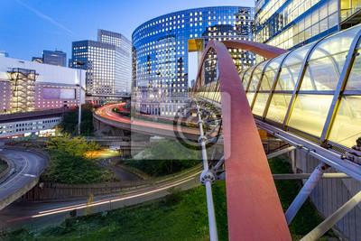 Puesta de sol y puente iluminado que unen dos edificios juntos en La Defense, el mayor distrito de negocios europeo situado en el oeste de París, Francia