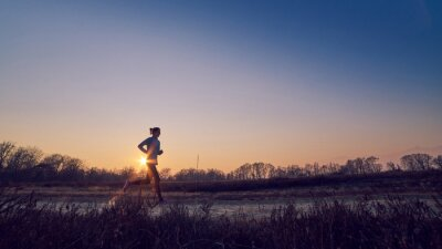 Cuadro Ragazza atletica si allena all'aperto su tierra di sera