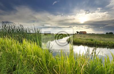Rayos de sol sobre casa, rio y prado