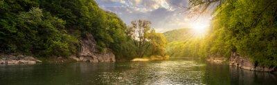 Cuadro río del bosque con las piedras en costas al atardecer