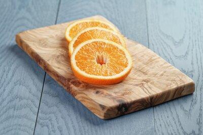 Cuadro Rodajas de naranja madura en tabla de corte de oliva, enfoque superficial