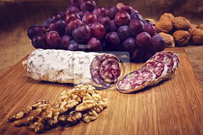 Cuadro Salami con nueces en un plato de madera con uvas