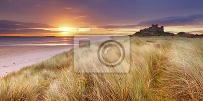 Salida del sol sobre las dunas en el castillo de Bamburgh, Inglaterra