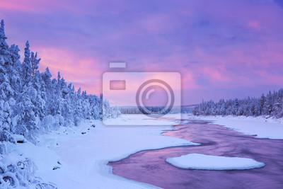 Salida del sol sobre los rápidos del río en un paisaje de invierno, la Laponia finlandesa