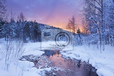 Salida del sol sobre un río en invierno cerca de Levi, Laponia finlandesa