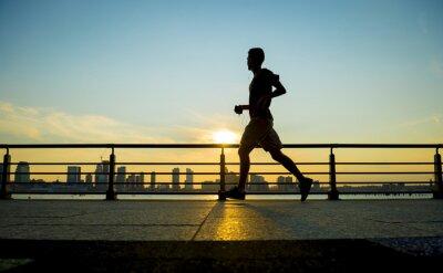Cuadro Silueta de corredor corriendo al atardecer frente al horizonte de la ciudad