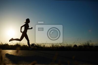 Cuadro Silueta de la muchacha atlética corriendo por el camino de una puesta de sol