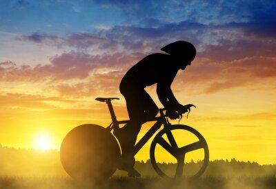 Cuadro Silueta de un ciclista en una bicicleta de carreras en la puesta del sol.