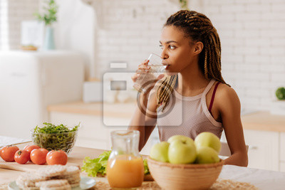 Cuadro Slim and fit woman drinking water before having breakfast