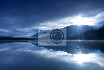 sol sobre las montañas y el lago alpino