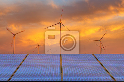 solar panels and windmills against a beautiful sky
