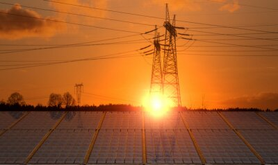 Solar panels with  electricity pylon at sunset. Clean energy concept