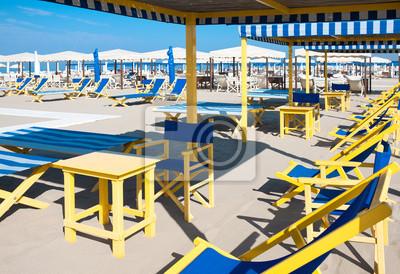 sombrillas, sillas de playa, tiendas de campaña en la arena por el mar