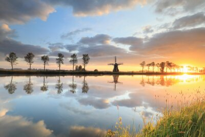 stunning sunrise over Dutch windmill by river