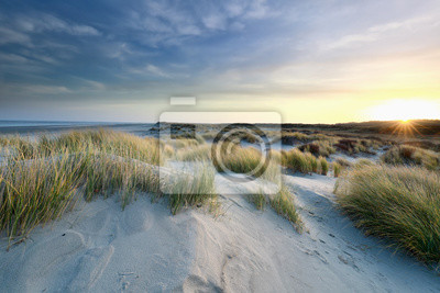 sunrise over sand dunes by north sea coast