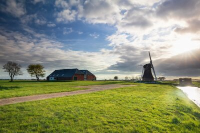 sunshine over windmill and farmhouses by river