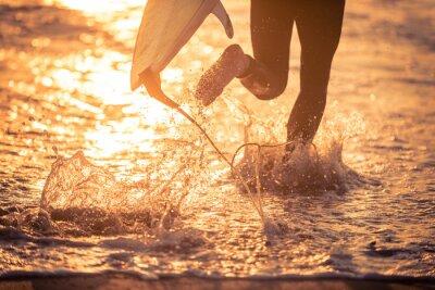 Cuadro Surfista corriendo en el agua con su tablero