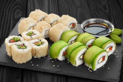 Cuadro Sushi rollos con aguacate, salmón y semillas de sésamo en la bandeja de pizarra.