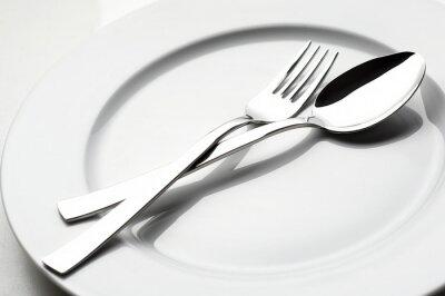 Cuadro tenedor y cuchara en el plato blanco