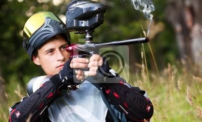 Tirador del Paintball que apunta el arma
