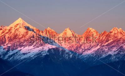 Cuadro tiro cercano de picos de montaña rojizos durante puesta del sol