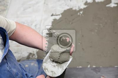 Cuadro Trabajador de la construcción está en el suelo de baldosas de piso de baldosas de adhesivo casa