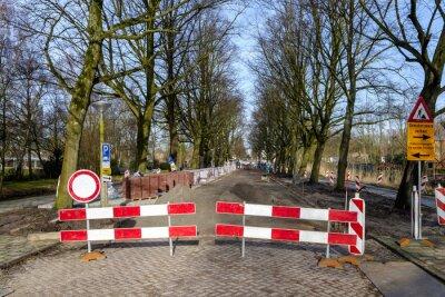 Trabajos de construcción en carretera, con barreras que bloquean la carretera, arena y materiales de construcción