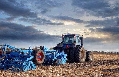 Cuadro Tractor trabajando en el campo al atardecer