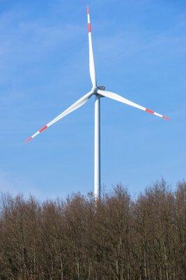 Turbina de viento detrás de una zona boscosa