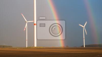 Turbinas de viento bajo un arco iris después de la tormenta y fuertes lluvias