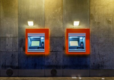 Two orange lined ATM machines on a concrete wall at night, with no people in sight