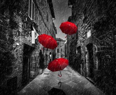 Cuadro Umrbellas volando con el viento y la lluvia en la calle oscura en una antigua ciudad italiana en la Toscana, Italia