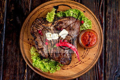 un bistec a la parrilla grande en una placa de madera, vista desde arriba