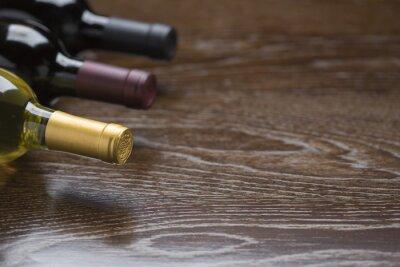 Cuadro Varias botellas de vino sobre superficie de madera reflectante Resumen