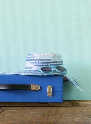 Cuadro vieja maleta azul de moda para los viajes y el sombrero de la playa