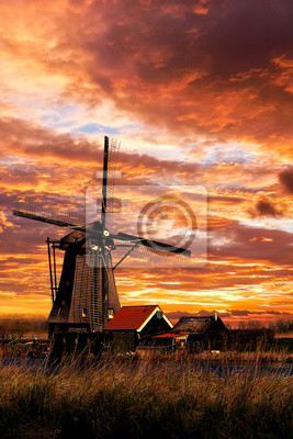 Warm and beautiful sunset on a windmill and its farm house keeper at Kinderdijk, Netherlands