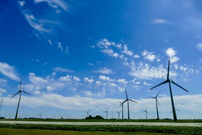 wind turbines in field with blue sky and clouds, in Sweden Scandinavia North Europe
