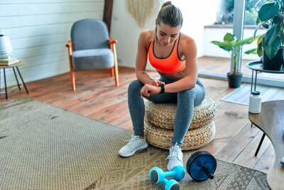 Cuadro Woman checking her workout time at home. Sport, fitness, lifestyle, technology and people concept - woman setting heart-rate watch.