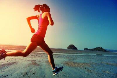 Cuadro young woman running on sunrise beach