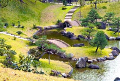 Fotomural Ajardinado jardín de rocas montañosas con pequeños puentes sobre arroyo sinuoso, cuesta arriba, pinos
