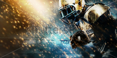 Fotomural American football sportsman player on stadium running in action. Sport wallpaper with copyspace.