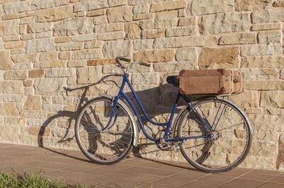 Fotomural Bicicleta de la vendimia y la maleta vieja en un muro de piedra